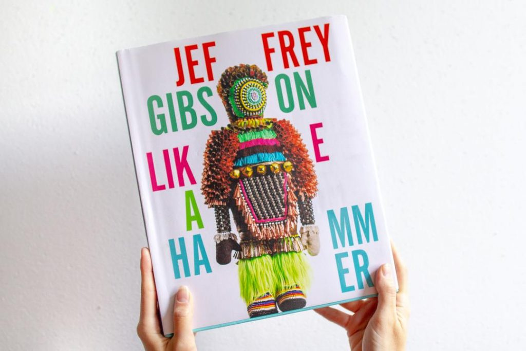 "Image of two hands holding up a book with a photo of a figurative sculpture and the title ""Jeffrey Gibson: Like a Hammer."""